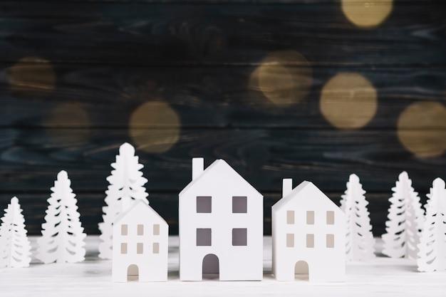 Casas de papel hechas a mano y abetos. Foto gratis