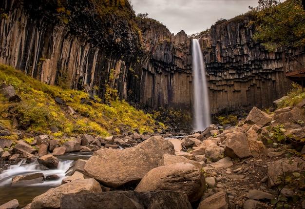 Cascada svartifoss rodeada de rocas y vegetación bajo un cielo nublado en skaftafell en islandia Foto gratis