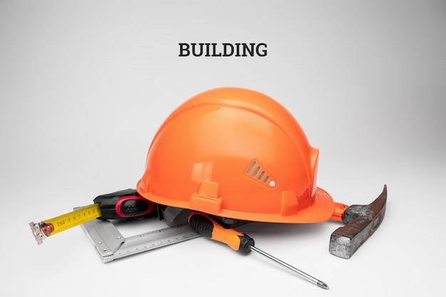 Casco de construcción blanco, cinta métrica, martillo, destornillador. construcción de la inscripción. concepto de arquitectura, construcción, ingeniería, diseño, reparación. Foto Premium