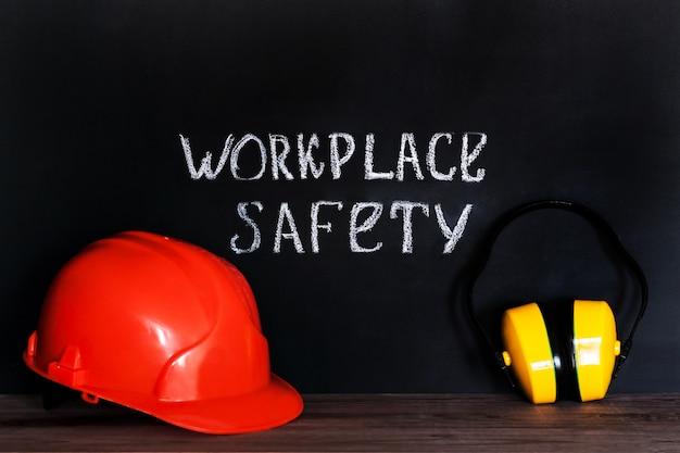 Casco de construcción sobre fondo negro con la inscripción seguridad en el trabajo. Foto Premium