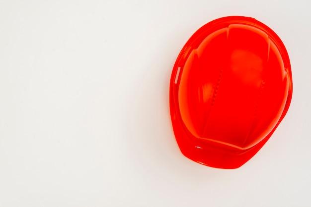 Casco plano de la construcción de color rojo sobre fondo blanco Foto gratis
