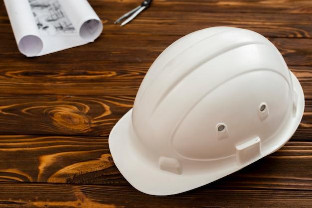 Casco plano de construcción con planos en el fondo. Foto gratis