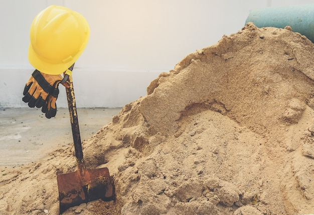Cascos amarillos, guantes y pala sobre la pila de arena. Foto Premium