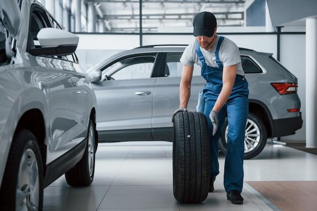 Casi termino. mecánico sosteniendo un neumático en el taller de reparación. reemplazo de neumáticos de invierno y verano. Foto gratis