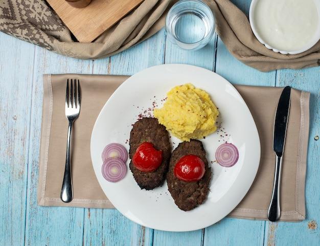 Casitas de carne con tomate a la parrilla y puré de papas Foto gratis