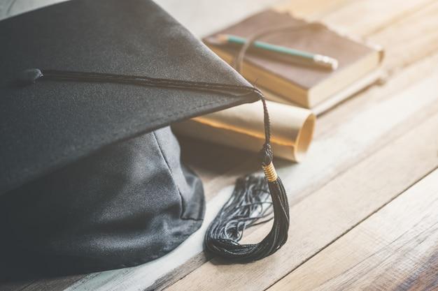 Casquillo de la graduación, sombrero con el documento del grado en el concepto de madera de la graduación de la tabla. Foto Premium