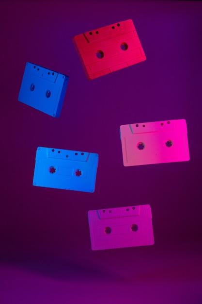 Cassettes de audio de colores colgando en el aire contra púrpura Foto Premium