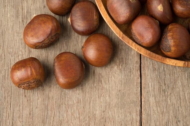 Castañas maduras en un tazón de madera en woden mesa.