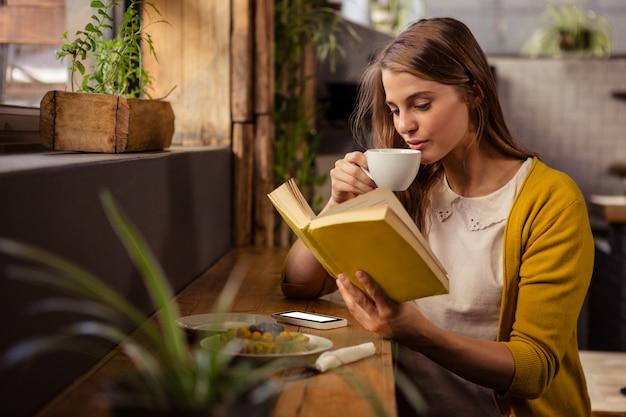 Casual mujer leyendo un libro mientras bebe Foto Premium