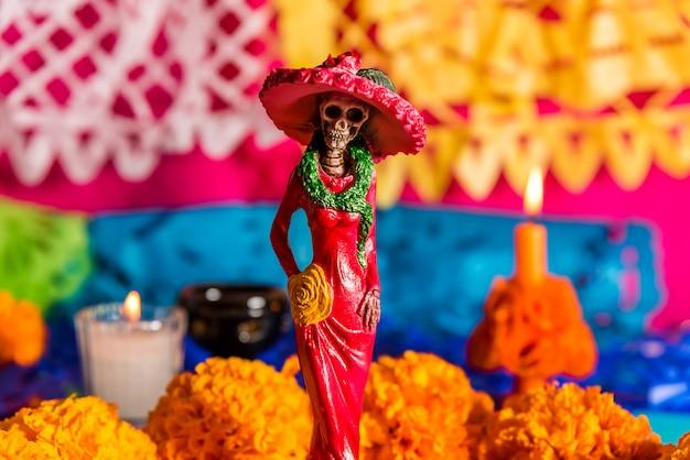 Catrina en el altar, con flores de cempasúchil y papeles picados, celebración del día de los muertos Foto Premium