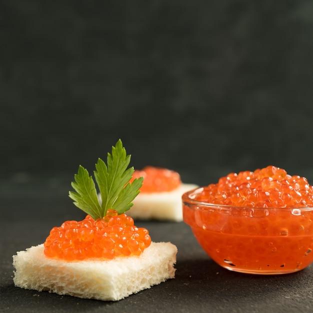 Caviar rojo en pan de trigo, mariscos. alimentación saludable y dieta. copiar espacio para texto Foto Premium