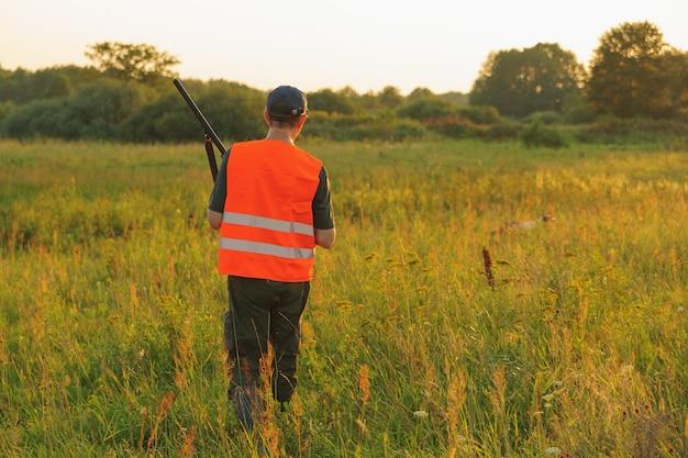 Cazador en la temporada de caza de otoño en puesta de sol. Foto Premium