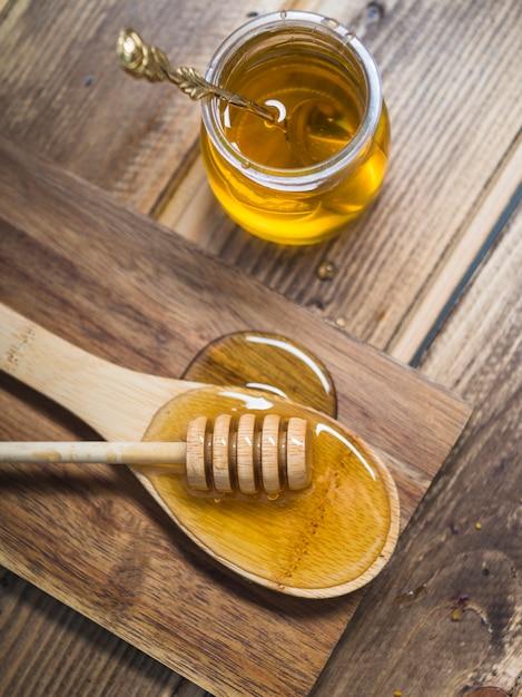 Cazo de miel fresca en una cuchara de madera y una olla con cuchara Foto gratis