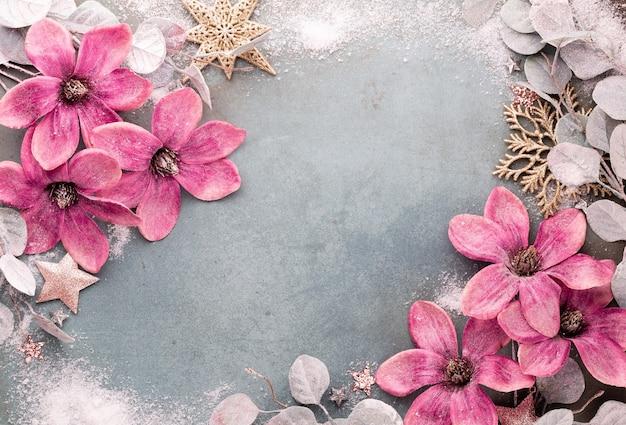 Celebración de año nuevo y fondo de navidad con flores rosas, nieve, estrellas y vista superior de adornos navideños. Foto Premium