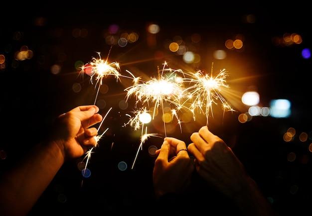 Celebrando con bengalas en la noche Foto gratis
