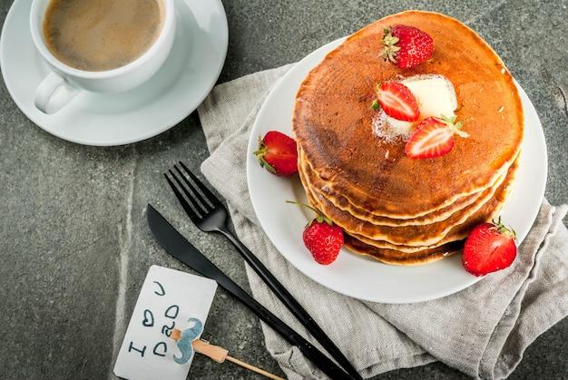 Celebrando el día del padre. desayuno. la idea de un desayuno festivo abundante y delicioso: panqueques con mantequilla, jarabe de arce y fresas frescas, con felicitaciones. taza de café. copyspace Foto Premium