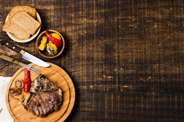 Cena con bistec en platos rústicos. Foto gratis