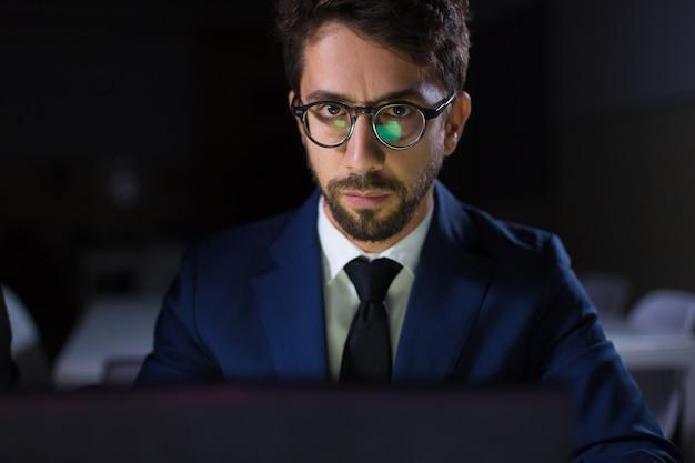 Centrado hombre sentado a la mesa con el portátil y mirando a cámara Foto gratis