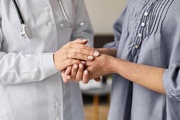 Centro de recuperación de covid doctora sosteniendo las manos del paciente anciano Foto gratis