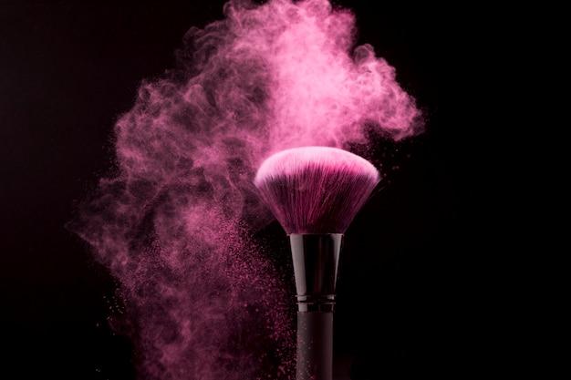 Cepillo cosmético en nube de polvo rosado sobre fondo oscuro Foto gratis