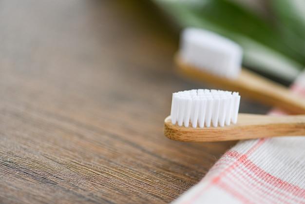 Cepillo de dientes de bambú en la tela ecológica, artículos libres de plástico natural y hoja verde Foto Premium