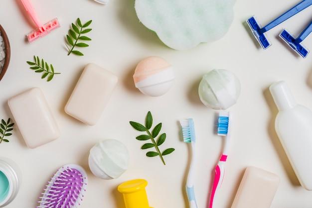 Cepillo de dientes; jabón; bomba de baño rosado; productos de maquinilla de afeitar y cosméticos sobre fondo blanco Foto gratis