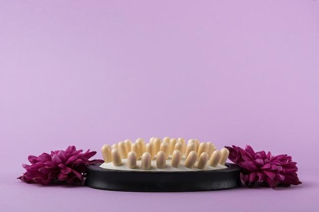 Cepillo de masaje con flores de color rosa sobre fondo morado Foto gratis