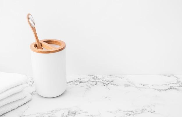 Cepillo y pila de toallas blancas sobre superficie de mármol. Foto gratis