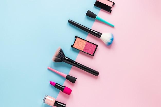 Cepillos en polvo con cosméticos en la mesa. Foto gratis