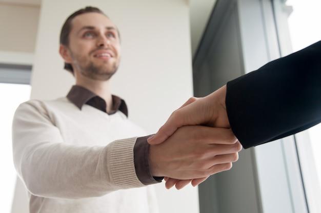 Cerca de apretón de manos, sonriente hombre de negocios y cliente estrechándole la mano Foto gratis