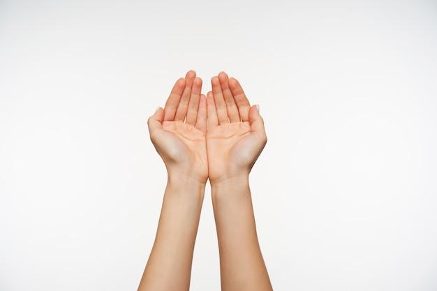 Cerca de atractivas manos de piel clara de mujeres jóvenes formando juntos gesticulando Foto gratis