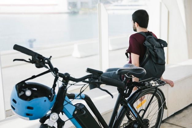 Cerca de bicicleta eléctrica con hombre sentado en el fondo Foto gratis