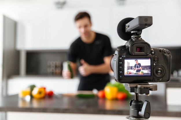Cerca de una cámara de video filmando joven blogger masculino sonriente Foto gratis