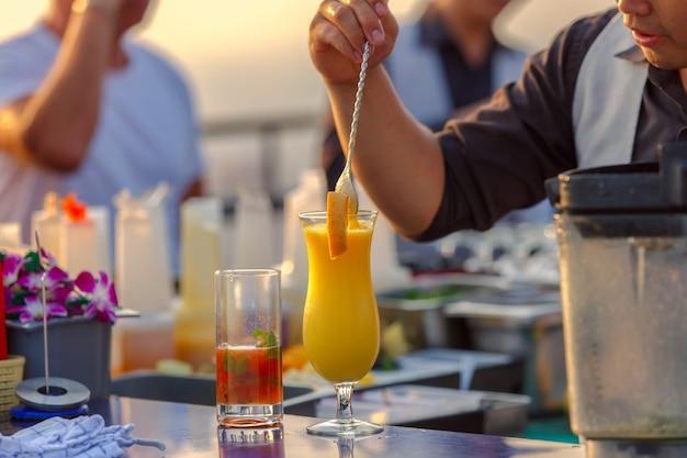 Cerca de los camareros en el proceso de preparación de la mezcla de jugo de naranja para los clientes Foto Premium