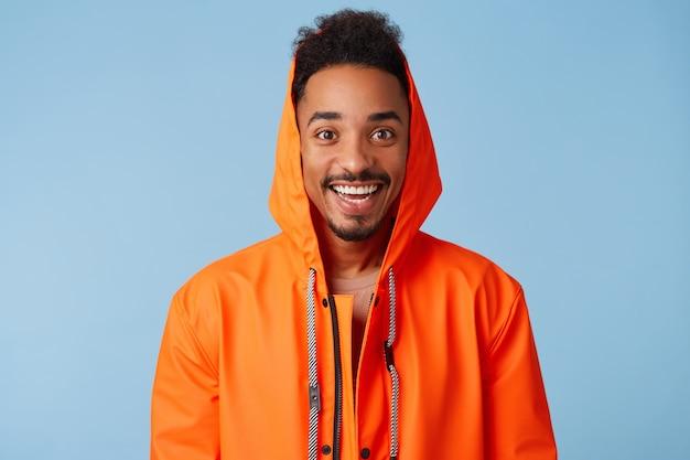 Cerca de un chico guapo afroamericano de piel oscura viste una capa de lluvia naranja, se siente feliz, sonríe ampliamente y se pone de pie. Foto gratis