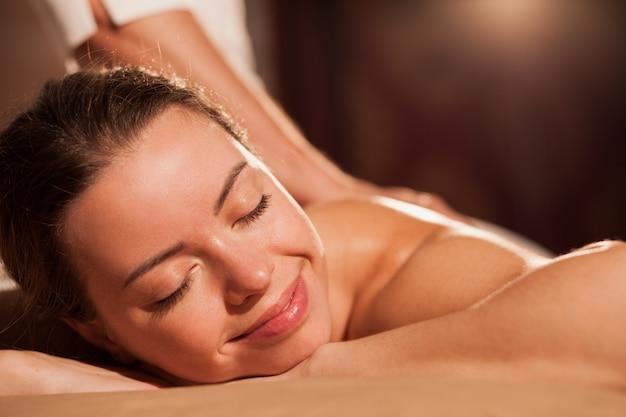 Cerca de una hermosa mujer joven feliz sonriendo con los ojos cerrados, disfrutando de un relajante masaje en el centro de spa. hermosa mujer relajante en el salón de mimos, copia espacio. servicio, viajes, turismo. Foto Premium