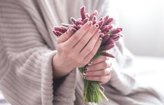 Cerca de hermosas manos femeninas con gran taza blanca de café capuchino y flores. Foto gratis