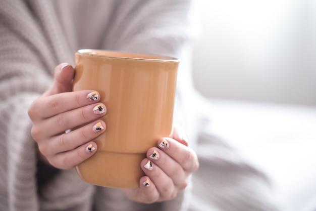 Cerca de hermosas manos femeninas sosteniendo una gran taza blanca de flores y café capuchino Foto Premium