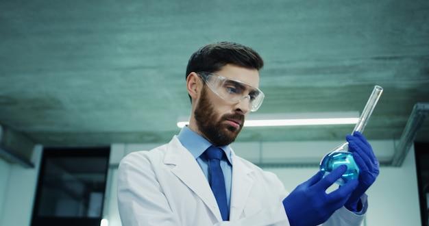 Cerca del hombre guapo del cáucaso, científico de laboratorio en las gafas y túnica blanca, mirando el tubo de ensayo con líquido azul mientras realiza el análisis. Foto Premium