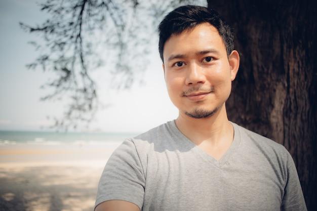 Cerca del hombre está de pie bajo el árbol de pino en la playa. Foto Premium