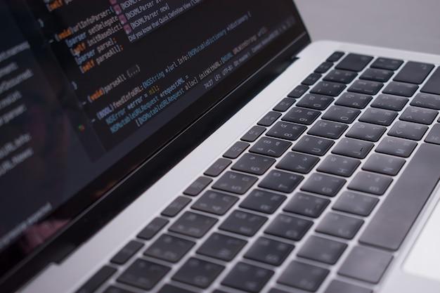 De cerca. la imagen muestra el código que los desarrolladores crearon un monitor de computadora en una mesa blanca. Foto Premium