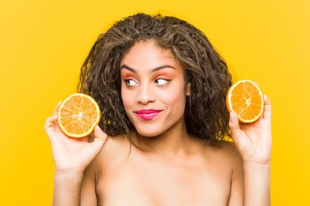 Cerca de una joven afroamericana hermosa y maquillaje mujer sosteniendo una toronja Foto Premium