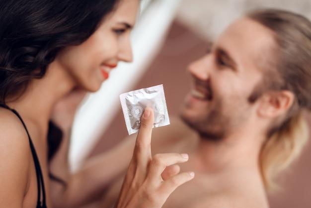 De cerca. joven apasionada tiene condón en la mano. Foto Premium