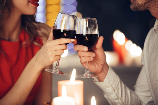 Cerca de la joven pareja copas con vino Foto gratis