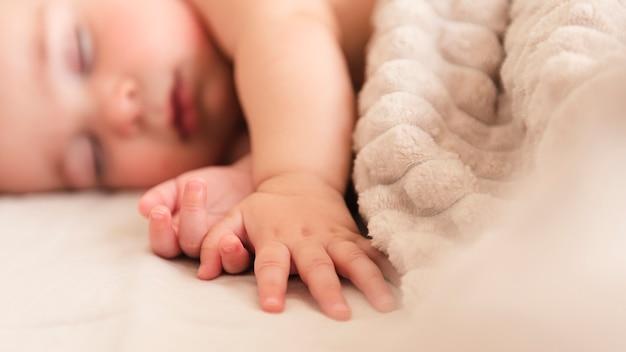 Cerca de la mano adorable bebé Foto gratis