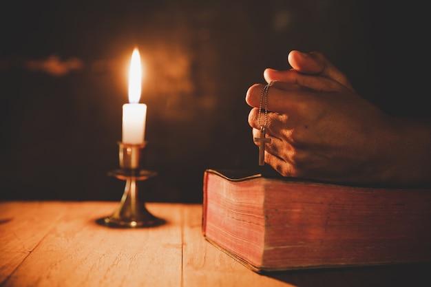 Cerca de la mano del hombre está orando en la iglesia con una vela encendida Foto gratis