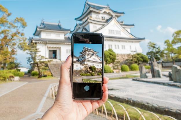 De cerca, la mano humana es una fotografía del castillo kishiwada en la ciudad de kishiwada, osaka Foto Premium