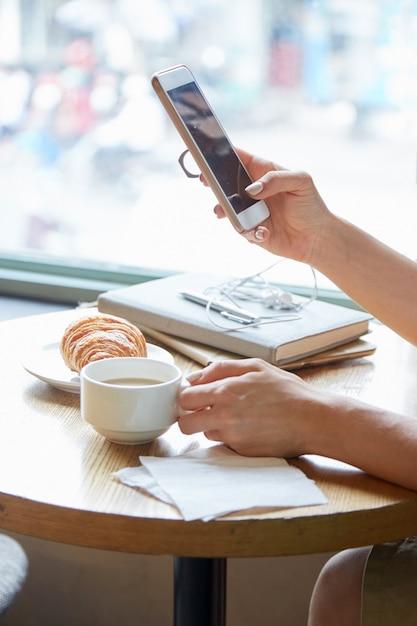 Cerca de manos femeninas irreconocibles sosteniendo el teléfono y la taza de café Foto gratis