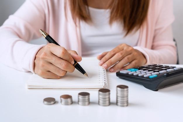 Cerca de la mujer asiática escribiendo en un portátil con calculadora y pila de monedas en el cuadro blanco Foto Premium