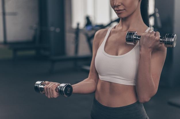 Cerca de una mujer atlética trabajando en el gimnasio, levantando pesas, copia espacio Foto Premium